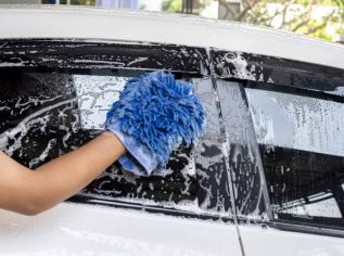 worker hand washing the exterior side window